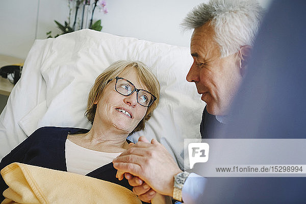 Smiling woman looking at senior partner while lying on bed in hospital ward