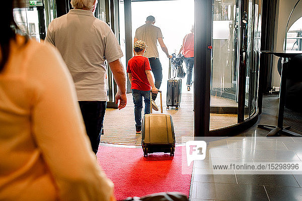 Rückansicht der Familie zu Fuß am Hotelausgang
