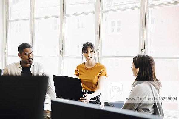 Weibliche Software-Ingenieurin erklärt ihren Kollegen  während sie im Büro am Fenster sitzt