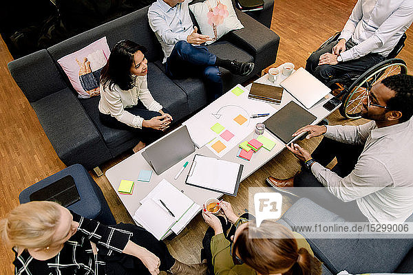 High angle view of sales managers talking during meeting at work place