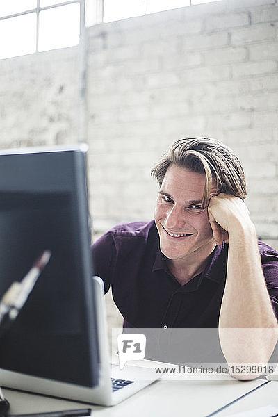 Porträt eines lächelnden jungen männlichen Programmierers  der am Schreibtisch im Büro kodiert