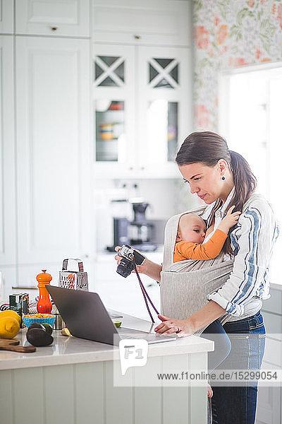 Seitenansicht einer Lebensmittel-Bloggerin mit Kamera  die einen Laptop benutzt  während sie ein kleines Mädchen in der Küche trägt