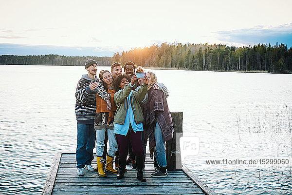 Glückliche Freunde  die sich mit einem Smartphone selbstständig machen  während sie bei Sonnenuntergang am Pier über dem See gegen den Himmel stehen