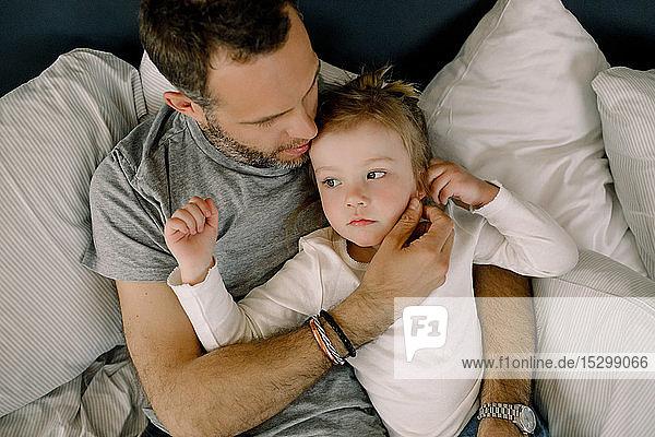 Direkt über der Aufnahme eines Vaters mit im Bett liegender Tochter Direkt über der Aufnahme eines Vaters mit im Bett liegender Tochter