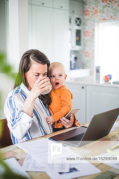 Working businesswoman drinking coffee while carrying yawning daughter in dining room