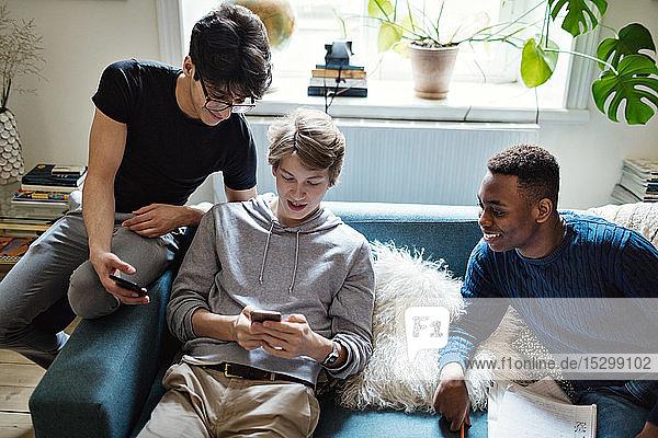 Schrägansicht von Social-Media-süchtigen Freunden  die während der Hausaufgaben im Wohnzimmer Smartphones auf dem Sofa benutzen Schrägansicht von Social-Media-süchtigen Freunden, die während der Hausaufgaben im Wohnzimmer Smartphones auf dem Sofa benutzen