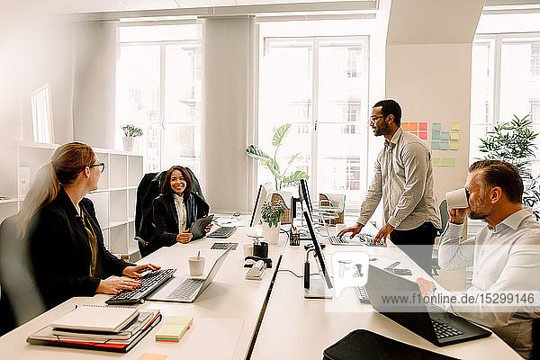 Sales managers brainstorming over business plans at desk in office