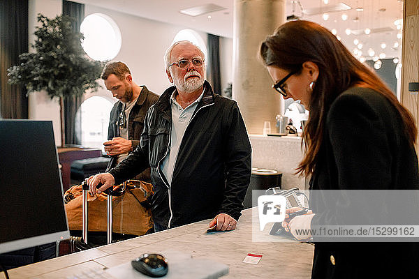Senior man looking away while standing with receptionist at reception in hotel