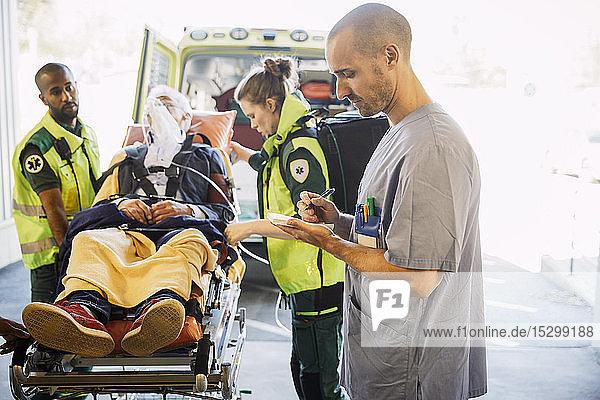Männliche Krankenschwester schreibt Bericht  während Sanitäter den Patienten im Krankenhaus auf die Trage schieben