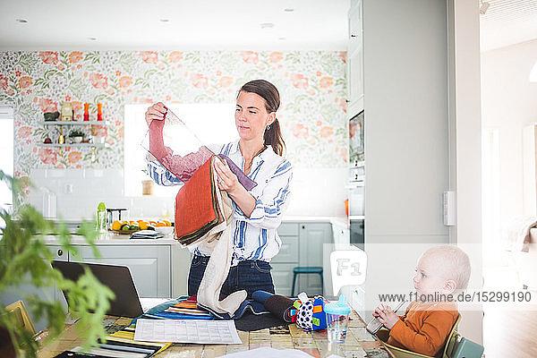 Berufstätige Mutter hält Stoffmuster in der Hand  während das Mädchen in der Küche im Heimbüro wegschaut Berufstätige Mutter hält Stoffmuster in der Hand, während das Mädchen in der Küche im Heimbüro wegschaut