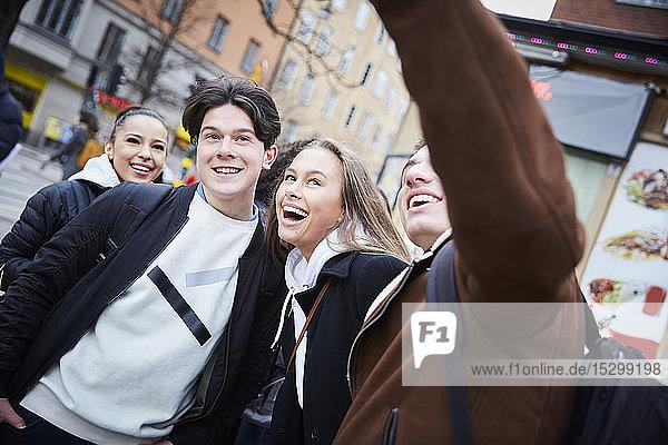Fröhliche Teenager-Jungen und -Mädchen genießen am Wochenende in der Stadt Fröhliche Teenager-Jungen und -Mädchen genießen am Wochenende in der Stadt