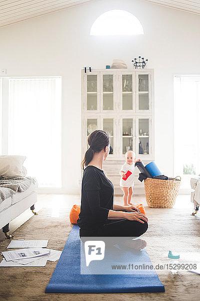Berufstätige Mutter übt Yoga in voller Länge aus  während die Tochter im Wohnzimmer spielt