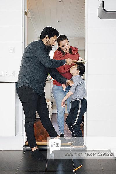 Vater und Mutter messen zu Hause die Körpergröße eines autistischen Sohnes an der Wand