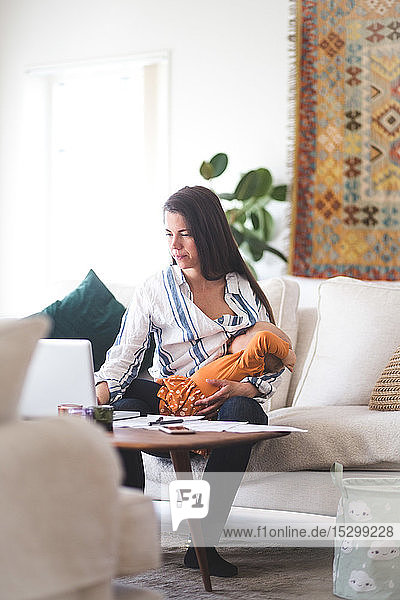 Working mother breastfeeding daughter while using laptop in living room at home office