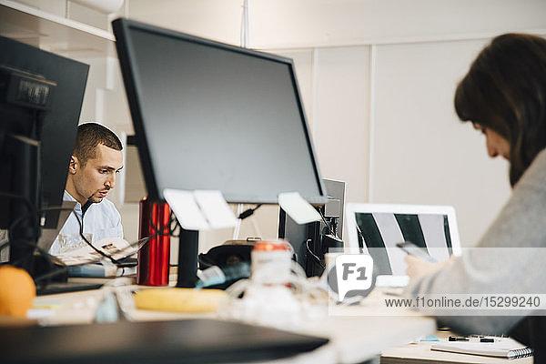 Weibliche und männliche Programmierer am Schreibtisch im Büro Weibliche und männliche Programmierer am Schreibtisch im Büro