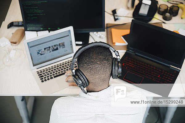 Rückansicht eines männlichen IT-Fachmanns  der einen Laptop am Schreibtisch benutzt  während er im Kreativbüro sitzt