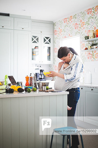 Female food blogger caring daughter while standing in kitchen at home