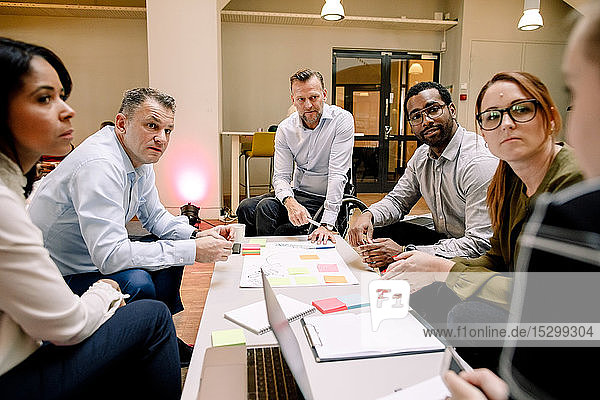 Sales executives looking at businesswoman during meeting in office