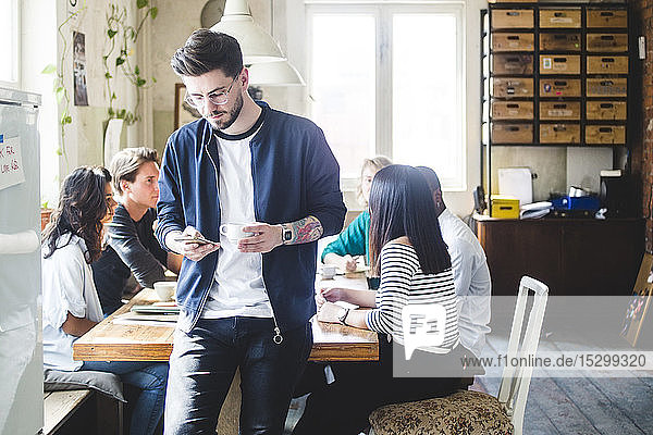 Young male professional using smart phone while IT programmers having meeting at desk in office