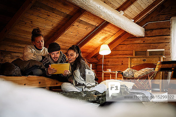 Male and female friends watching movie over digital tablet while relaxing in cottage