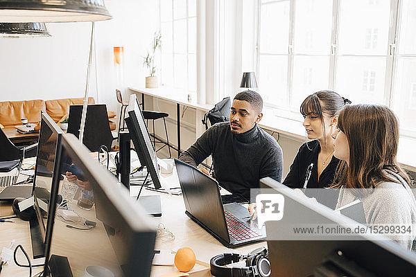 Hochwinkelansicht von IT-Fachleuten  die über einen Laptop auf einem Schreibtisch im Büro diskutieren Hochwinkelansicht von IT-Fachleuten, die über einen Laptop auf einem Schreibtisch im Büro diskutieren