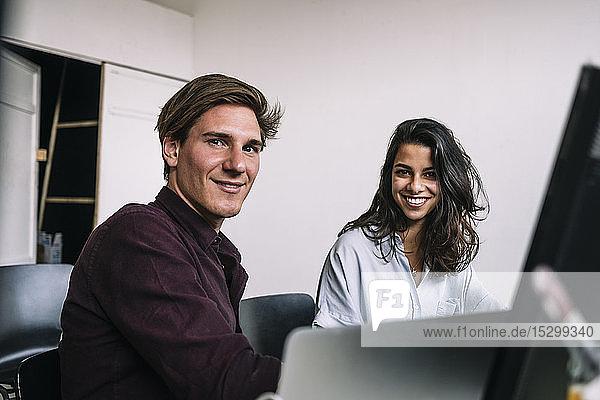 Porträt selbstbewusster männlicher und weiblicher IT-Profis am Schreibtisch im Kreativbüro
