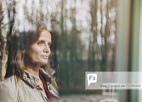 Lächelndes reifes weibliches berufliches Denken beim Blick durchs Fenster im Büro