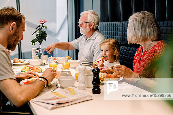 Smiling girl looking at father while having food with grandparents at restaurant