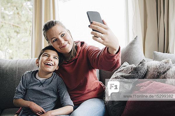 Lächelnde Mutter  die mit ihrem autistischen Sohn Selbsthilfe nimmt  während sie zu Hause auf dem Sofa sitzt