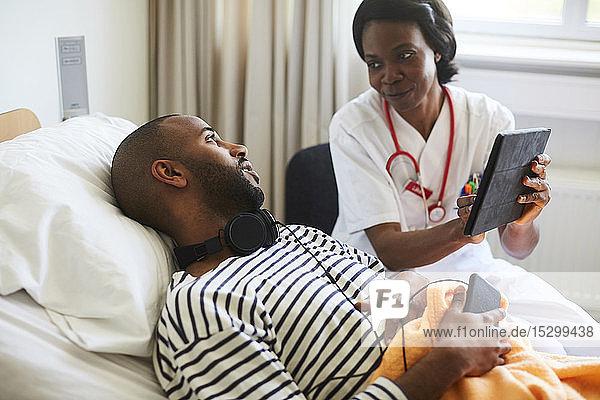Ärztin zeigt junger Patientin digitales Tablett während eines Besuchs auf der Krankenhausstation