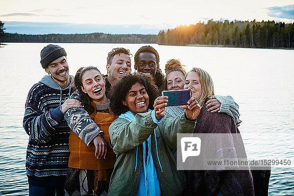 Glückliche männliche und weibliche Freunde  die bei Sonnenuntergang am See stehen und sich mit einem Smartphone selbstständig machen