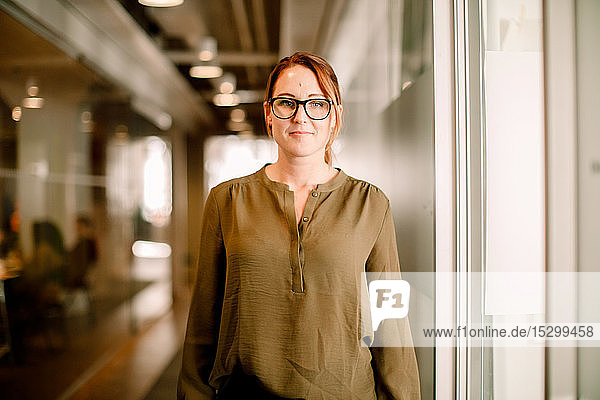 Porträt einer weiblichen Führungskraft  die eine Brille trägt und lässig elegant am Arbeitsplatz steht Porträt einer weiblichen Führungskraft, die eine Brille trägt und lässig elegant am Arbeitsplatz steht