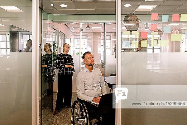 Kollegen  die einen Geschäftsmann beobachten  der Haftnotizen an die Glaswand im Sitzungssaal klebt