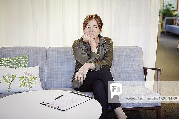 Portrait of confident smiling female psychologist sitting on sofa at workshop
