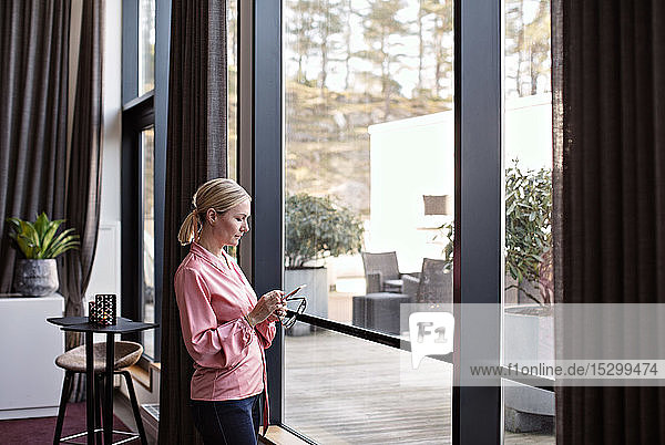 Businesswoman using phone while standing by window in office