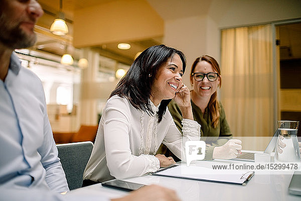 Cheerful businesswomen sitting at conference table during sales meeting in office