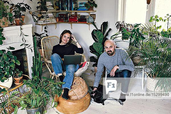 Porträt eines lächelnden Paares mittlerer Erwachsener mit Mops im häuslichen Zimmer Porträt eines lächelnden Paares mittlerer Erwachsener mit Mops im häuslichen Zimmer