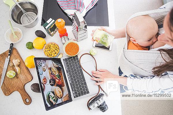 Schrägansicht einer Frau mit Einfluss auf das Essen  die während des Stillens eines Mädchens in der Küche bloggt Schrägansicht einer Frau mit Einfluss auf das Essen, die während des Stillens eines Mädchens in der Küche bloggt