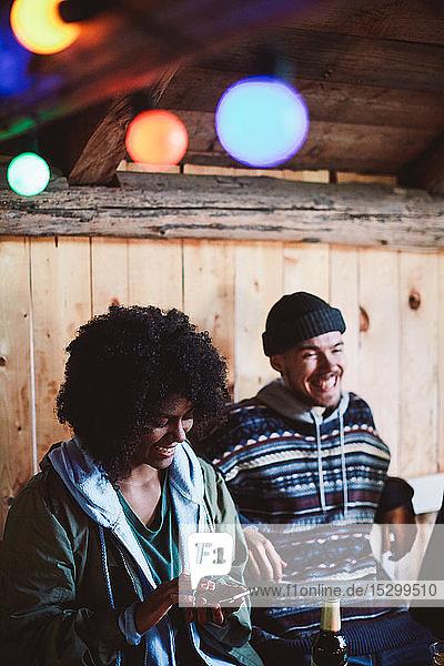 Lächelnde junge Frau benutzt Smartphone  während sie mit einem männlichen Freund in einer Hütte sitzt Lächelnde junge Frau benutzt Smartphone, während sie mit einem männlichen Freund in einer Hütte sitzt