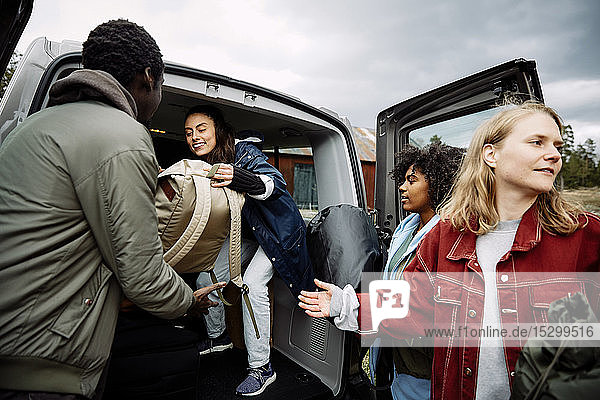 Smiling female passing backpacks to friends while standing in car