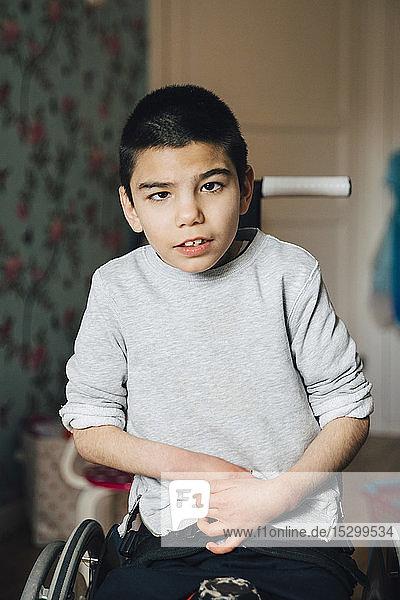 Portrait eines behinderten Jungen  der zu Hause im Rollstuhl sitzt