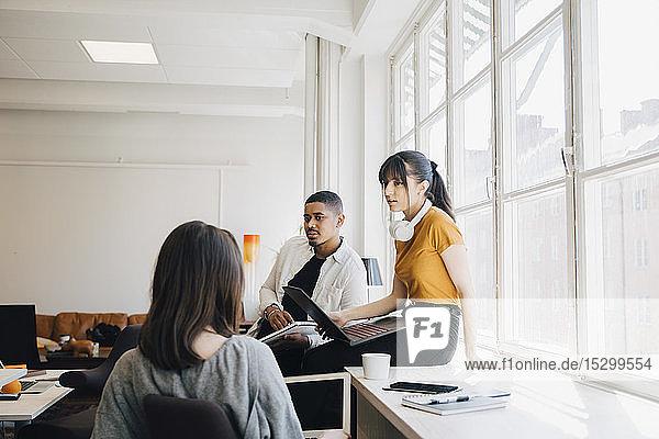 Computeringenieurin diskutiert mit Kollegen  während sie im Büro am Schreibtisch sitzt