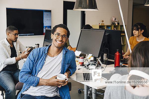 Porträt eines männlichen Computerprogrammierers  der von Kollegen am Schreibtisch im Büro sitzt