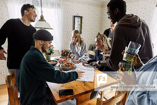 Glückliche Freunde stellen zu Hause Essen und Getränke auf den Holztisch