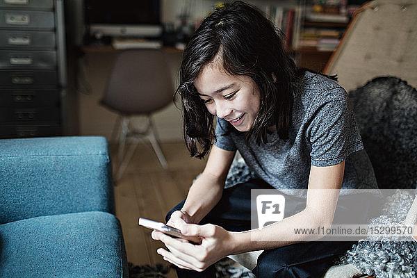 Social-Media-süchtiger lächelnder Junge  der ein Mobiltelefon benutzt  während er zu Hause sitzt
