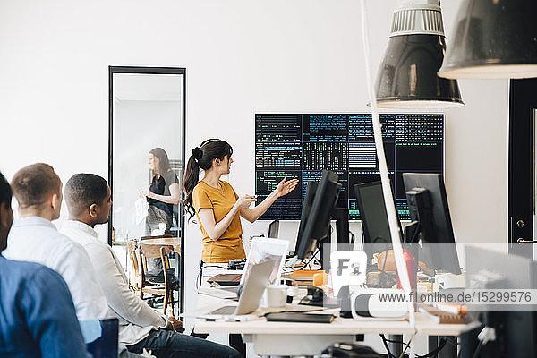 Weibliche Computerhackerin präsentiert Code auf dem Fernsehbildschirm während eines Treffens mit Programmierern im Kreativbüro