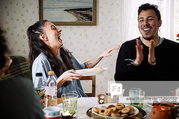 Junge Frau lacht  während sie einen männlichen Freund im Haus beim Händeklatschen beobachtet