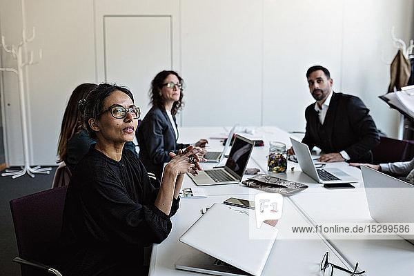 Geschäftsleute  die am Konferenztisch sitzen und sich während der Sitzung im Sitzungssaal konzentrieren