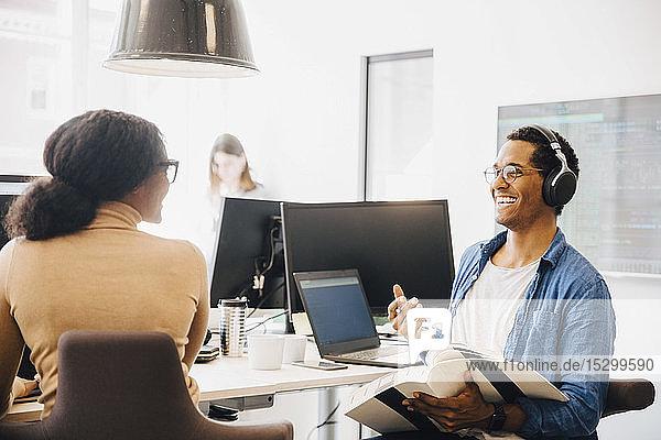 Fröhlicher männlicher Computerhacker im Gespräch mit weiblicher Mitarbeiterin am Schreibtisch im Kreativbüro
