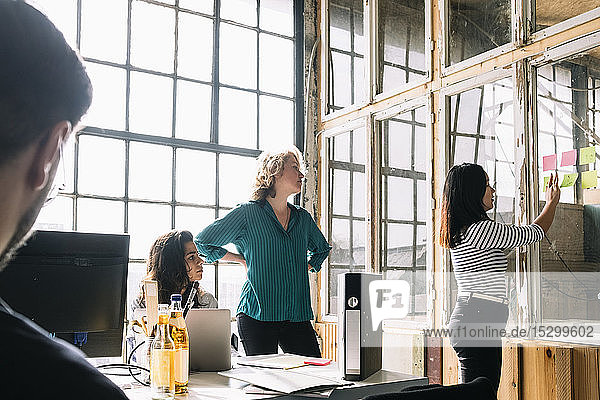 Kollegen betrachten Geschäftsfrau  die während einer Sitzung Haftnotizen an die Glaswand im Sitzungssaal klebt